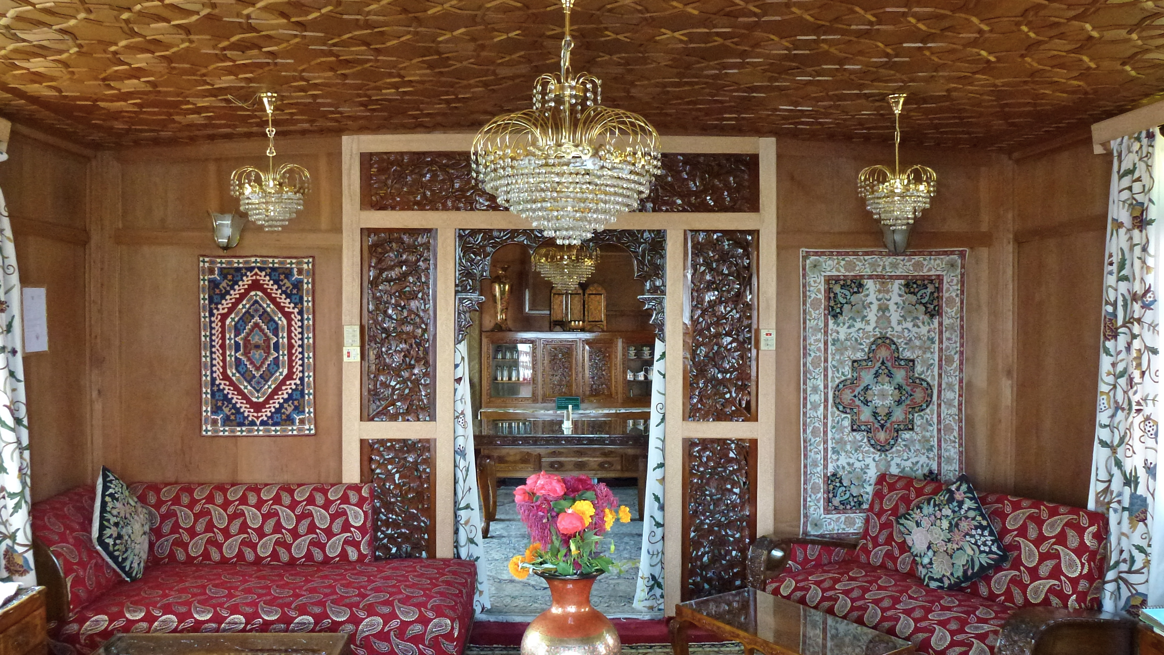 The lounge and dining room were an eclectic mix of various crafts woven rugs and fabrics laquered carved woodwork papier mache laquerwork and kashmiri